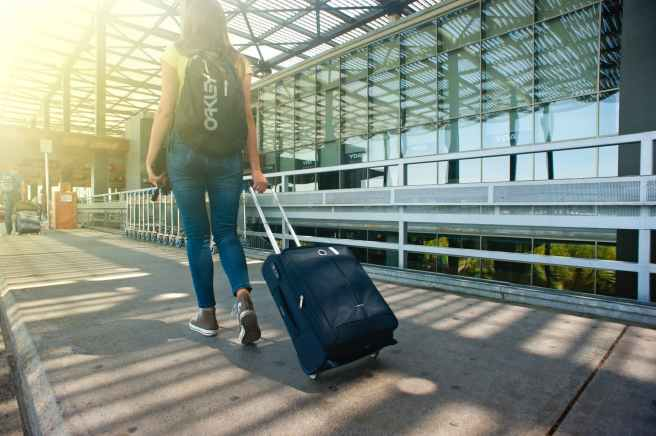 woman walking on pathway while strolling luggage