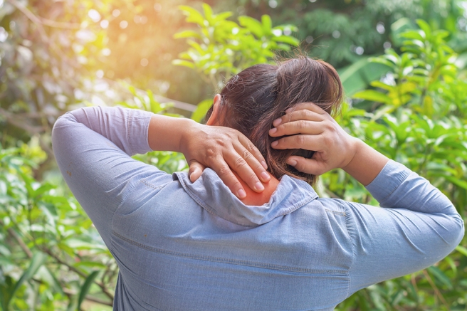 woman suffering from neck pain at outdoor. healthy concept